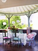 Tablecloth on table and white wooden chairs on dark wooden terrace with white, circular wooden roof