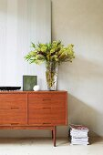 Objets d'art and vase of flowers on sixties sideboard next to stack of magazines