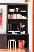 Small home office in dark fitted shelving niche with Scandinavian wooden stool and hammered copper pot as waste paper basket