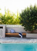 Wooden bench integrated into garden wall next to swimming pool