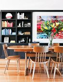 Oak dining table and bouquet of lilies in front of dark living room shelving with integrated painting
