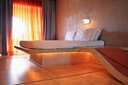 Futuristic bedroom with downlit bed and adjoining concrete bathtub; translucent curtains at window in background