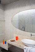 Washstand with white china basin on stepped concrete surface and oval mirror on concrete wall