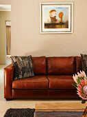 Framed picture above brown leather sofa; arrangement of protea flowers in foreground