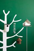 Various bird feeders and nesting boxes hung on white. stylised wooden tree against wooden wall