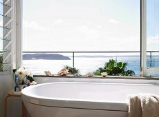 Bathroom with glorious sea view though open, folding glass window; seashell ornaments on edge of bathtub