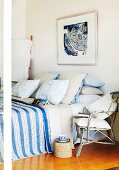 Wicker chair next to French bed with stacks of pillows and blue striped bedspread below framed picture on wall
