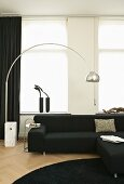 Living room decorated in black and white with designer arc lamp