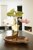 Gold, designer vase of orchids and anthuriums on dining table