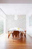 White dining table, classic wooden chairs, patterned wallpaper on end wall and glass wall to one side in minimalist room