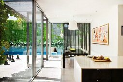 Open-plan kitchen and dining area next to continuous glass wall; view of sunny terrace and pool with climber-covered back wall
