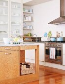 Island counter with wooden base unit in corner of modern kitchen