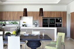 Open-plan designer kitchen with calm colour scheme in grey, white and wood-toned elements on wall units; dining table with pedestal leg and upholstered chairs in foreground