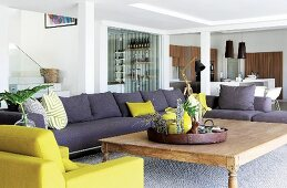 Sofa combination in grey and lime green with large wooden table in open-plan interior with staircase, bar and kitchen in background