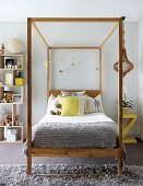 Teenager's bedroom in pale grey with lemon yellow accents and wooden bed with canopy