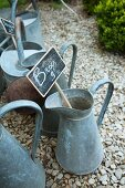 Old zinc jugs with price labels on a gravel path