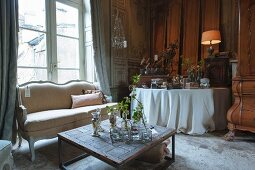 A sales exhibition of living room furniture and antique-style accessories in the parlour of an old French country house