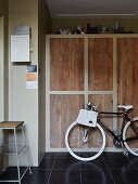 Bicycle in utility room in front of fitted cupboards with simple oak doors