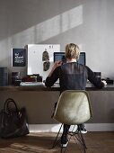 Woman sitting on Eames chair at desk in grey-painted home office