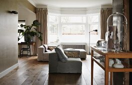 Interior in warm shades of grey and wood with sofa combination in front of bay window; display cabinet in foreground
