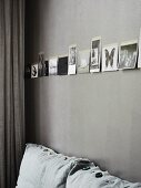 Black and white photos on grey-painted wall above sofa with various decorative buttons
