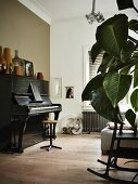Old piano decorated with vases opposite sofa with houseplant leaves and rocking chair in foreground