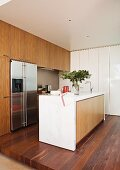 Designer, fitted kitchen with stainless steel fridge and island counter on wooden platform; white, glossy cupboards, marble and wooden fronts