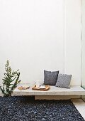 Scatter cushions, tea tray and stationary on minimalist bench made from stone slab in courtyard with dark gravel floor
