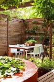 Circular raised bed with red mosaic tiles; secluded seating area with elegant screen fencing on terrace in background