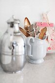 Thermos flask and china jug of kitchen utensils on stone surface