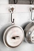 Metal pots and pans hanging from flower-shaped wall hooks