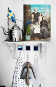 Vintage kettle next to painted family portrait on bracket on white wooden wall