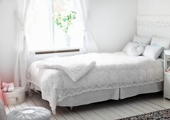 White, lacy bedspread on bed below window in rustic interior