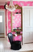 Black, leather lounge chair at console table and framed mirror on wall with butterfly-patterned wallpaper on pink background