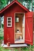 View in through open door of Swedish outdoor toilet in wooden hut painted falu red