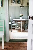 Dining area with simple wooden chairs and retro lamp in kitchen of old, Swedish wooden house