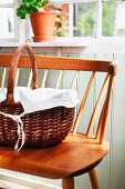 Handled basket lined with white cloth on 50s wooden bench in porch of Swedish wooden house