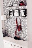 Schwarz-Weiss-Rot: An floral gemusterte Tapetenwand angelehnte Figuren mit Zwergenmützen, darüber Kinderfotos und ein Deko-Bord