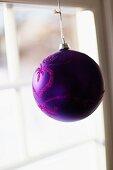 Violette Christbaumkugel mit Glitzerdruck vor Fenster aufgehängt