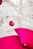 Kissen, Weihnachtskugel und Zierkette in leuchtendem Magenta an weißem, künstlichem Christbaum