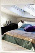 Doppelbett mit Tagesdecke und Kissen unter Dachflächenfenstern im Vintage Schlafzimmer
