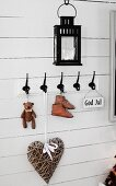 Collection of vintage nick-nacks hanging from coat pegs on white wooden wall
