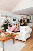 Family on and behind sofa next to decorate Christmas tree in open-plan, rustic interior