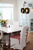 Table and chairs, some with white loose covers, in front of wreaths hanging on cupboard door