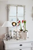 Table lamp with white lampshade and potted plant in front of wood-framed, lattice mirror on rustic chest of drawers