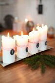 Lit white candles on metal tray