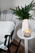 Ornate metal candle lantern in front of white water jug of fir branches on side table next to black rocking chair
