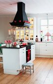 Black extractor hood above kitchen counter with white base unit on wooden floor in Scandinavian country-house kitchen