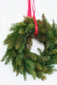 Wreath of fir branches hanging from red ribbon