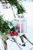 Lantern, apples and fir branches on rustic wooden stand in snowy garden